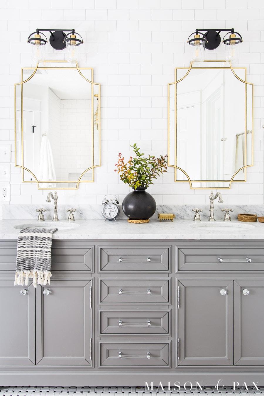 gray bathroom vanity in black and white tile bathroom