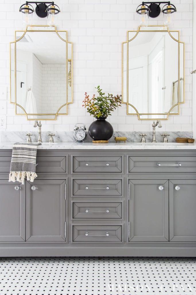 gray vanity with black and white basketweave tile floor