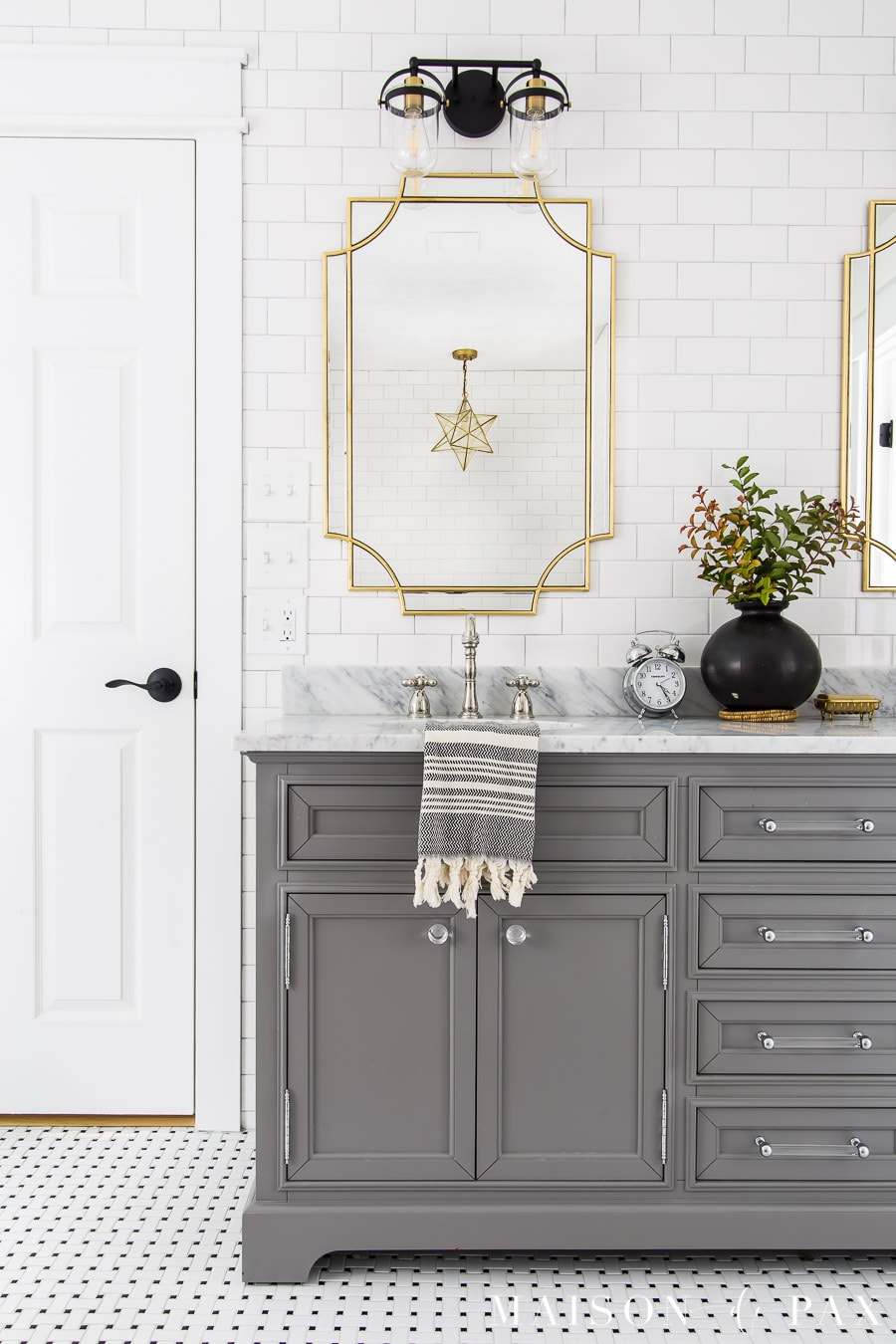 gray master bathroom vanity with gold mirrors and black and gold lights