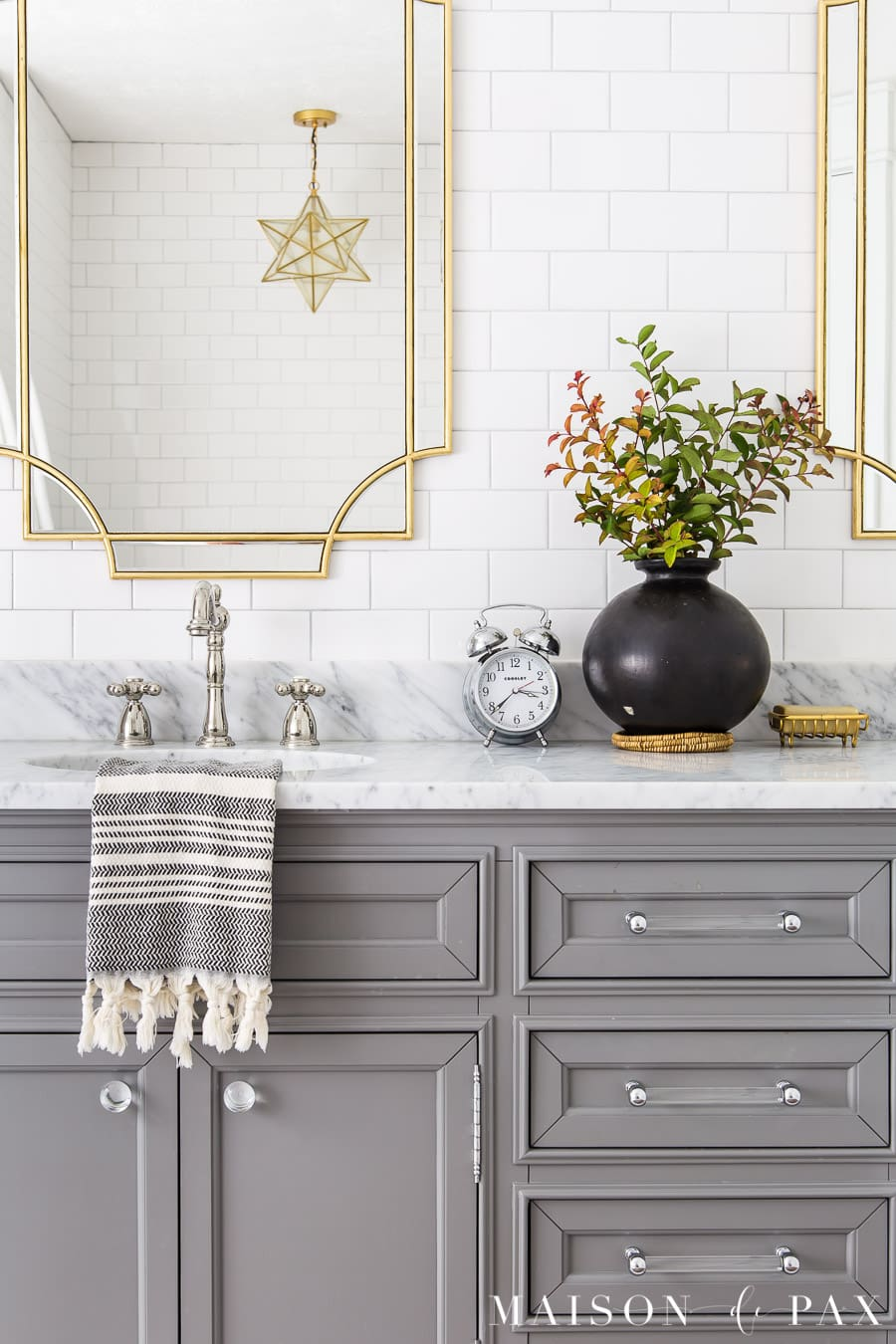 marble top vanity with polished nickel faucets and gold mirrors