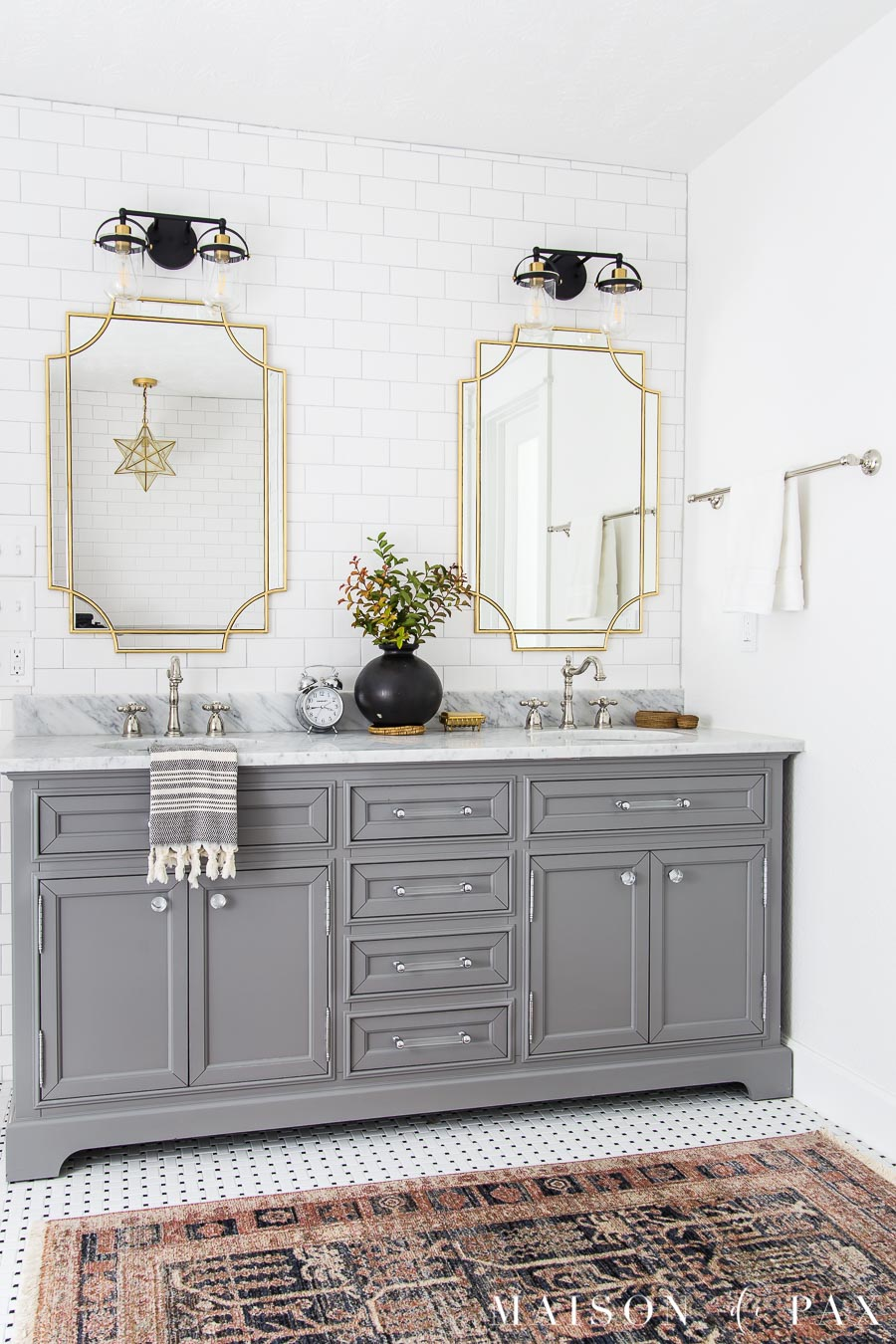 gray vanity in white tiled bathroom with polished nickel accessories and gold light fixtures