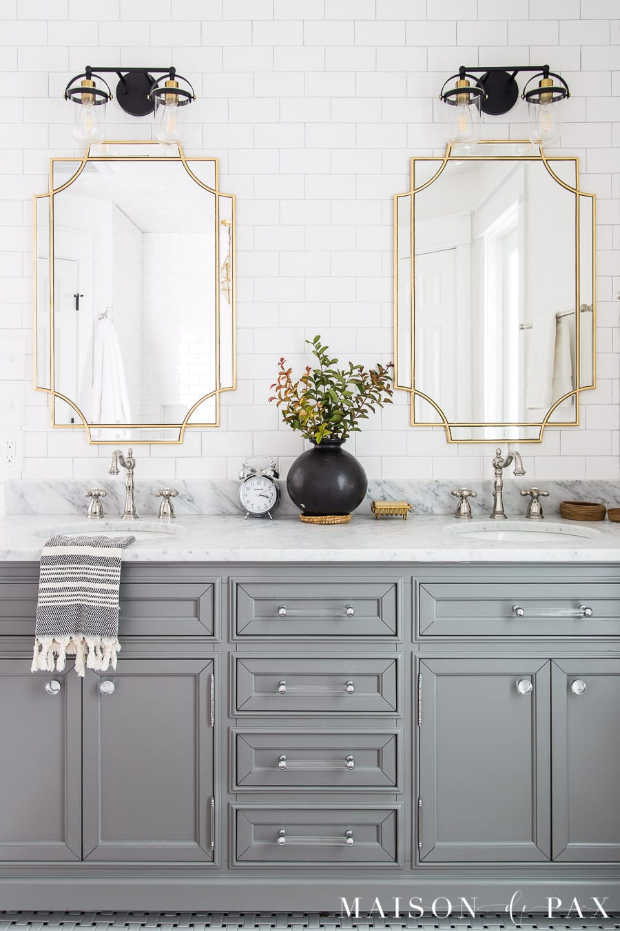 gray bathroom vanity with marble top and gold mirrors