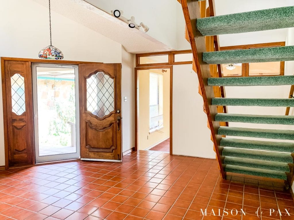 entryway with orange wood stairs