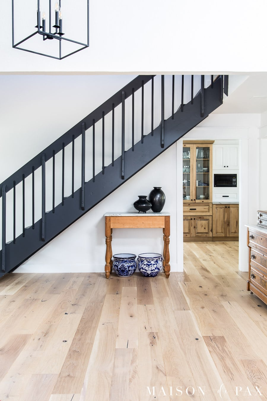 light wood floors, white walls, black stairs with black iron balusters